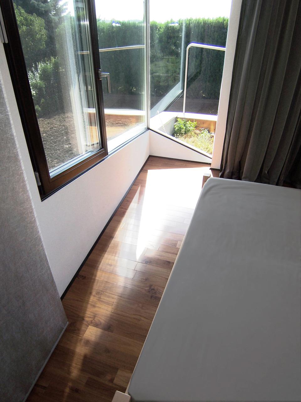 Helle Schlafräume mit großzügigem Ausblick in einem Einfamilienhaus der Paschinger Architekten