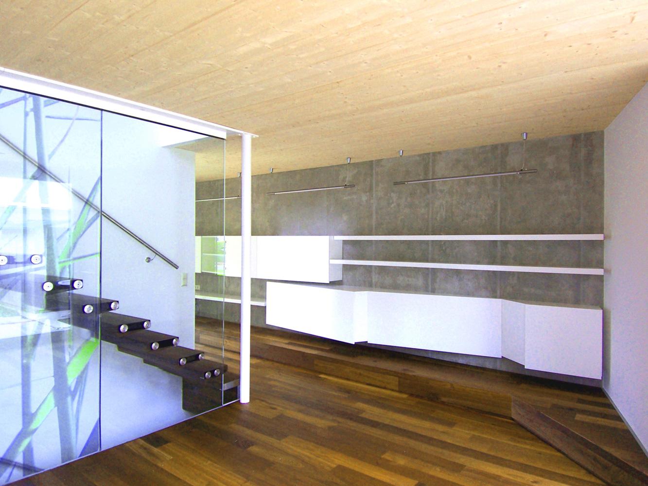 Innenansicht eines Doppelhauses an der alten Donau mit Holz-Glas-Stiege und besonderer Stauraum-Lösung an der Wand
