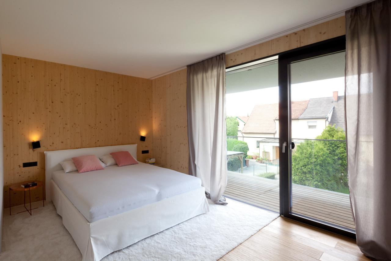 Schlafzimmer mit großer Terrassentüre und Ausblick über die Nachbarschaft (Paschinger Architekten)