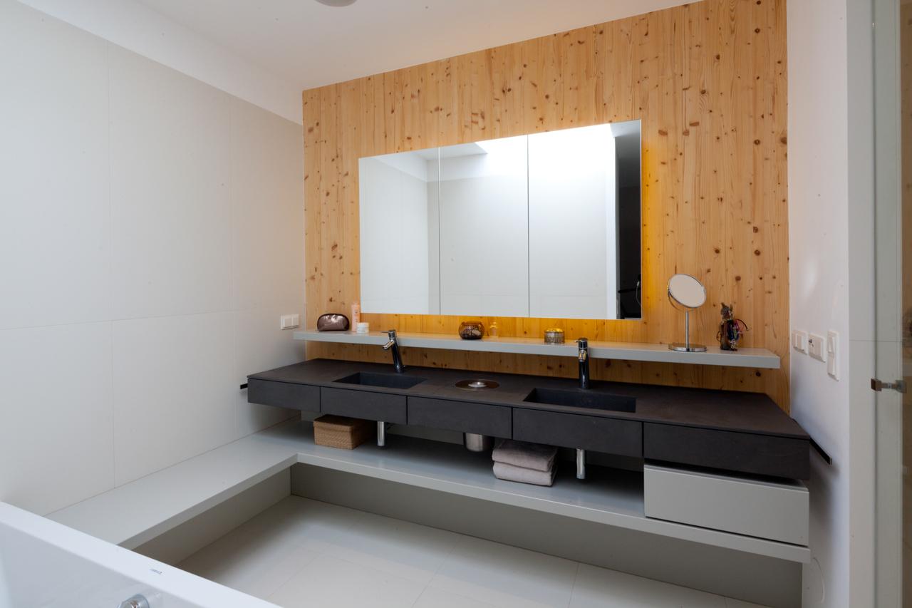 Von den Paschinger Architekten geplantes Badezimmer mit eigenen Waschbecken und Ablagemöglichkeiten