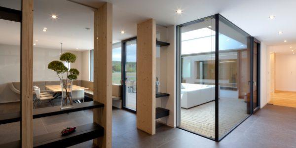 Ausblick in einen Innenhof mit großer Glasfront in einem Bungalow, der von Architekten geplant wurde