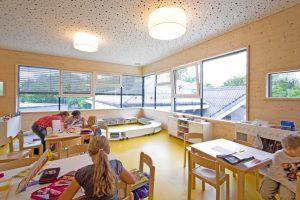 Gruppenraum mit Kindern im Kindergarten in Modulbauweise und Massivholzbauweise / kigago (Paschinger Architekten)