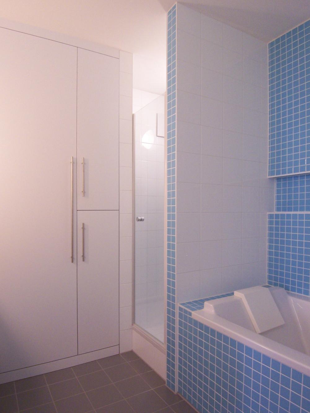 Bild des Bades mit integriertem Möbeldesign (Stauraum-Schränken & Badewanne) von einem Einfamilienhaus das von Architekten geplant wurde