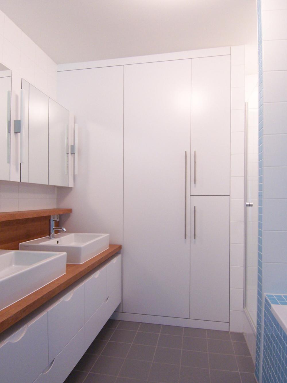 Bild des Bades mit integriertem Möbeldesign (Waschtisch & Stauraum-Schränken) von einem Einfamilienhaus das von Architekten geplant wurde