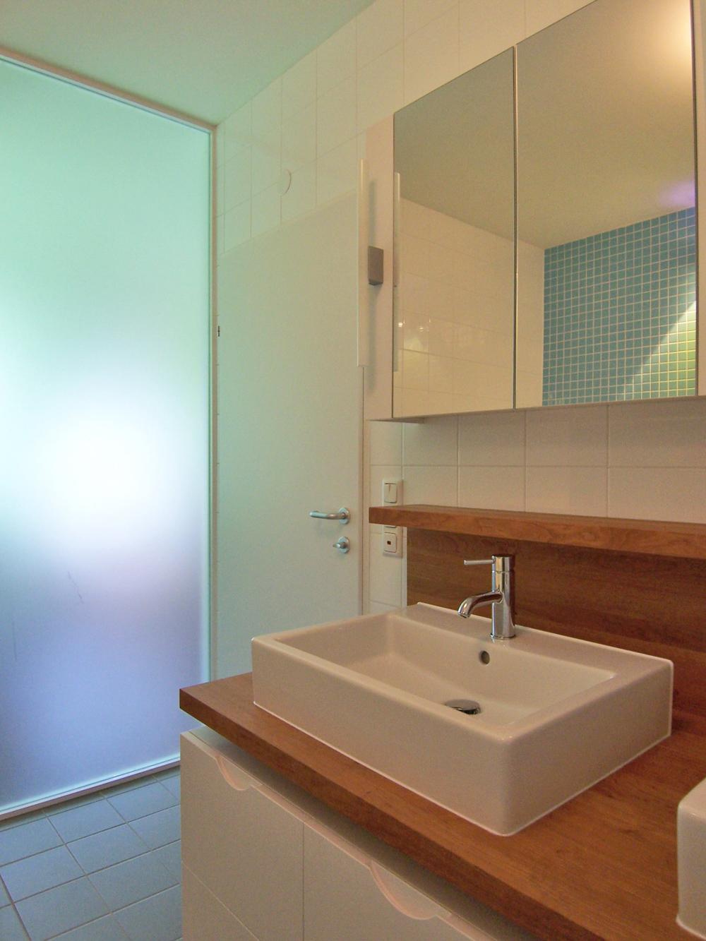Bild des Bades mit integriertem Möbeldesign (Waschtisch) von einem Einfamilienhaus das von Architekten geplant wurde