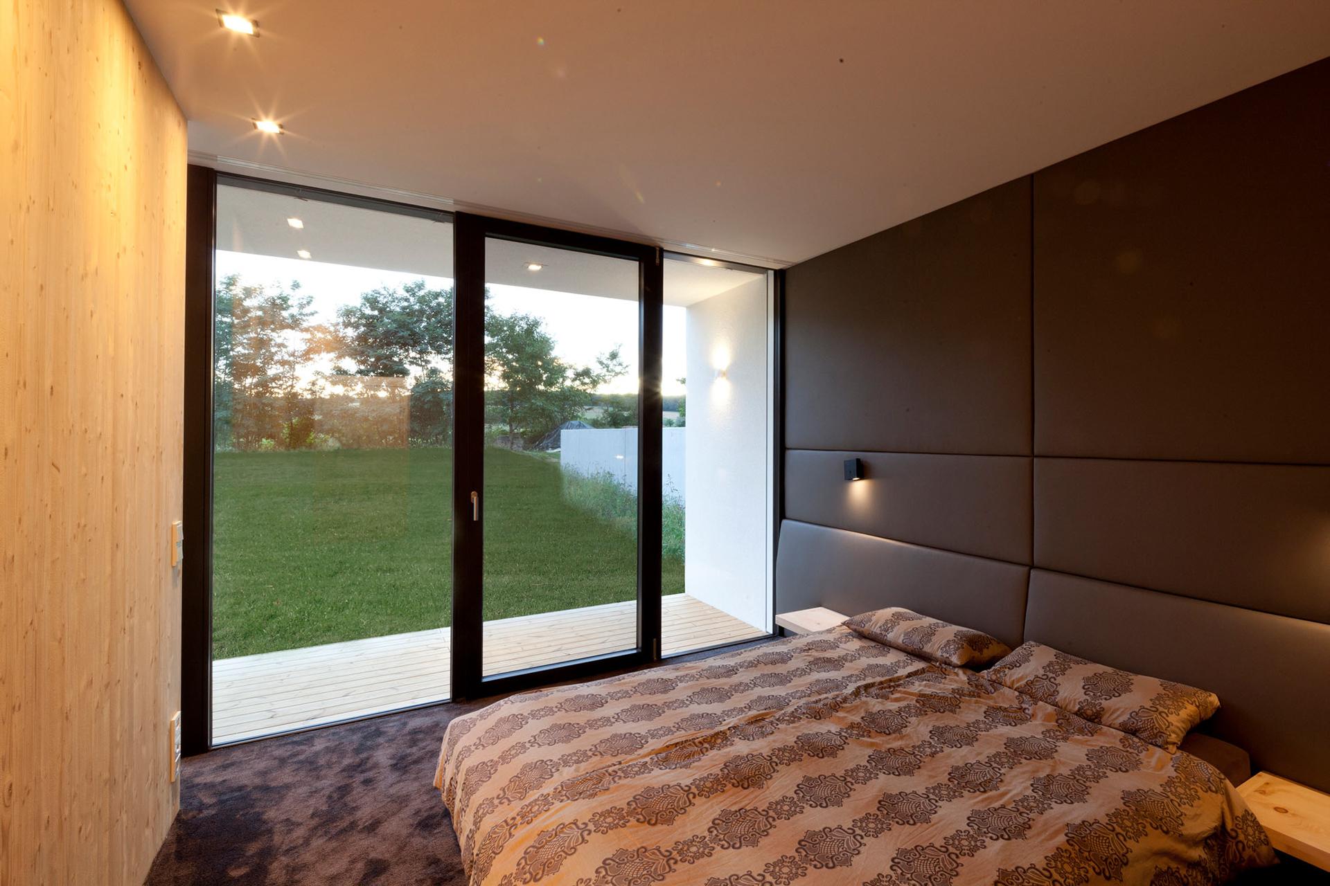 Innenansicht des Schlafzimmers mit Ausblick in einem Bungalow der Paschinger Architekten