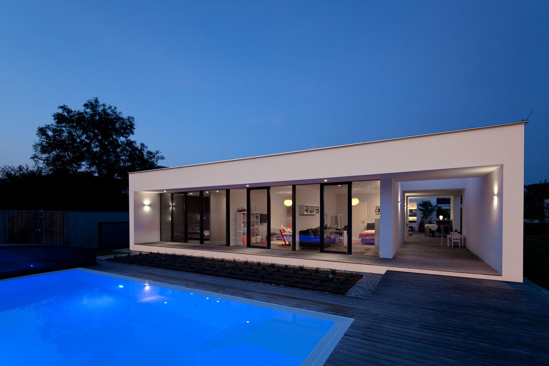 Stimmungsvolle, abendliche Außenansicht eines Bungalows der Paschinger Architekten