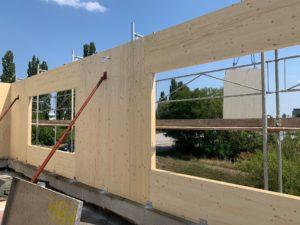 Detailansicht einer Holzmassivbau-Wand an der Außenseite des Rohbaus, die gerade eingerichtet und montiert wird