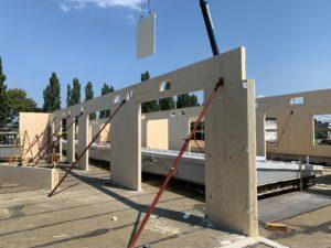 Innenansicht des Rohbaus bei dem Holzmassivwände gerade per Kran eingehoben, aufgestellt und eingerichtet werden