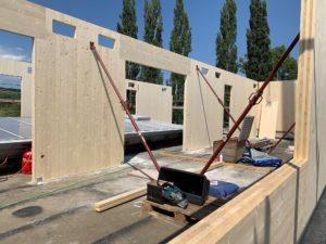 Innenansicht des Rohbaus bei dem Holzmassivwände gerade aufgestellt und eingerichtet werden