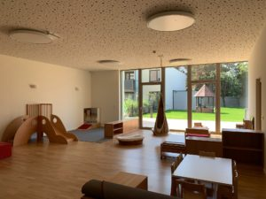 Ansicht eines Gruppenraumes mit Ausblick auf den Garten im Kindergarten für die St. Nikolaus Stiftung